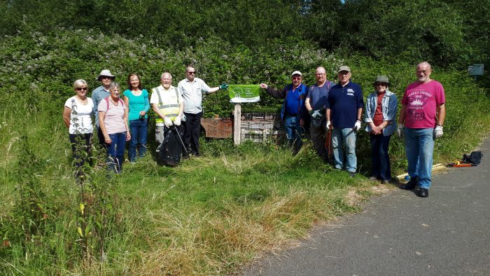 Members of Wapley Bushes Conservation Group showing off their eighth Green Flag Community Award at one of the Bug Hotels during their July work morning at the Local Nature Reserve.