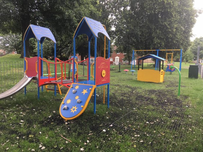 Photo of play equipment at Woodchester toddler play area including a multiplay and swings